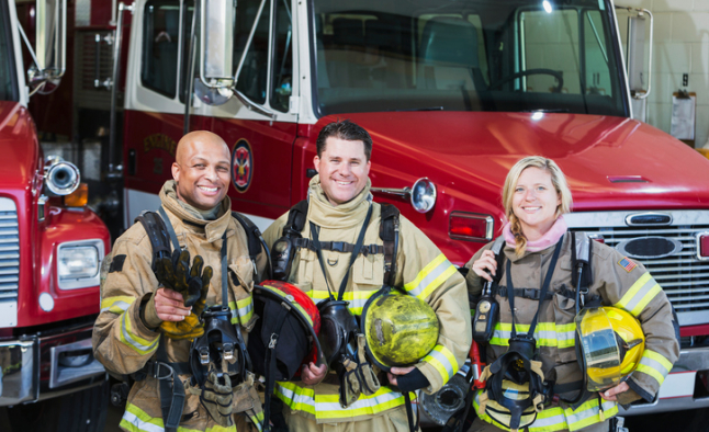 Three firemen smiling with heir helmets off standing in front of two firetrucks