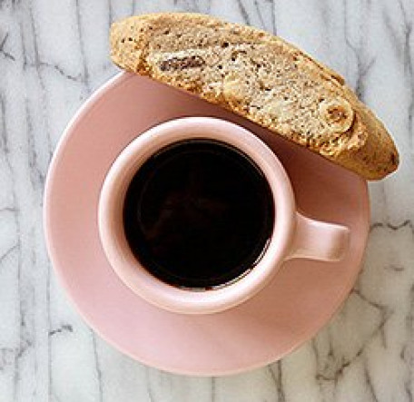 coffee in a pink cup and saucer with side of biscotti