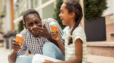 father and daughter eating ice cream and laughing