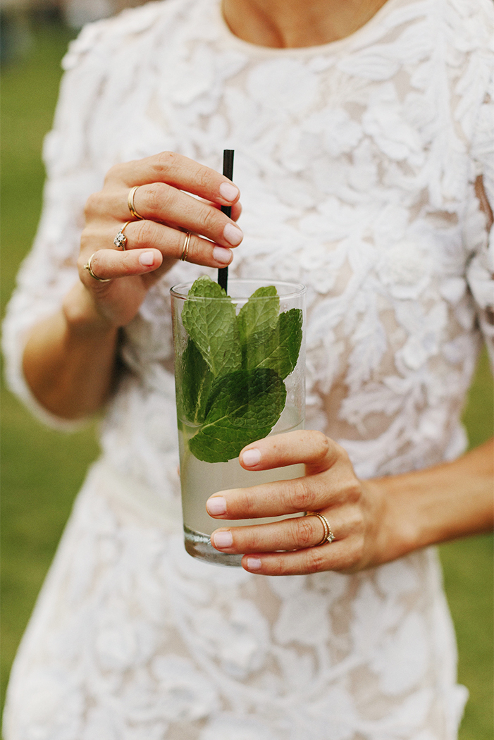 close up of a woman wearing a white dress holding a cocktail with mint leaves