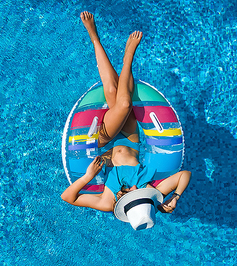 woman lounging in a pool on a float