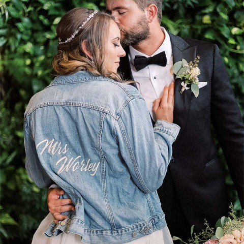 couple hugging and the bride is wearing a jean jacket with her new last name on it