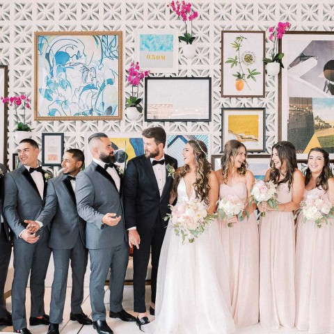 wedding party standing in front of wall of murals