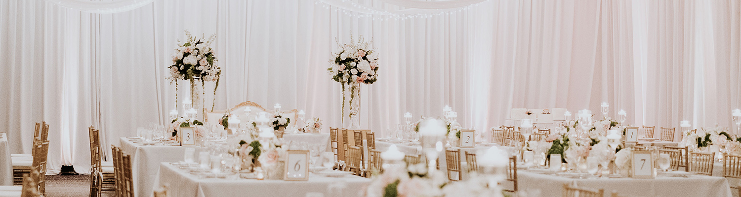 wedding reception with multiple tables and white cloths
