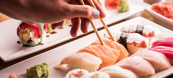 women using chopsticks to grab fresh sushi