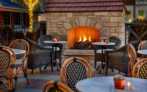 a lit outdoor fireplace and outdoor seating with tables