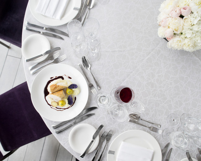 a table set up with a plated dish and glass of red wine