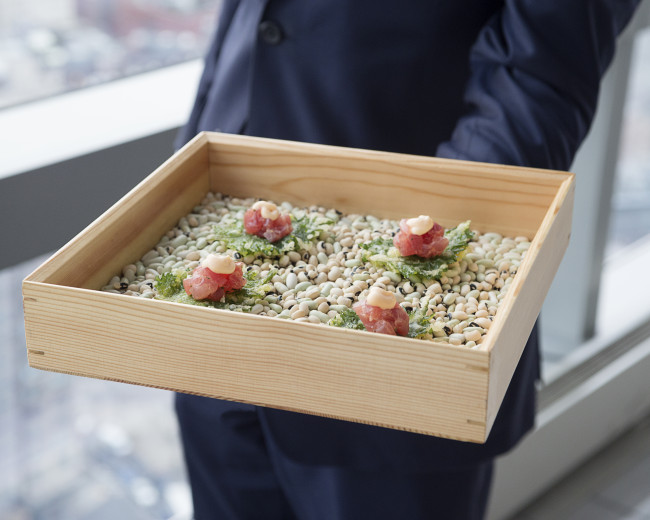 a box with appetizers in it being served  by waiter