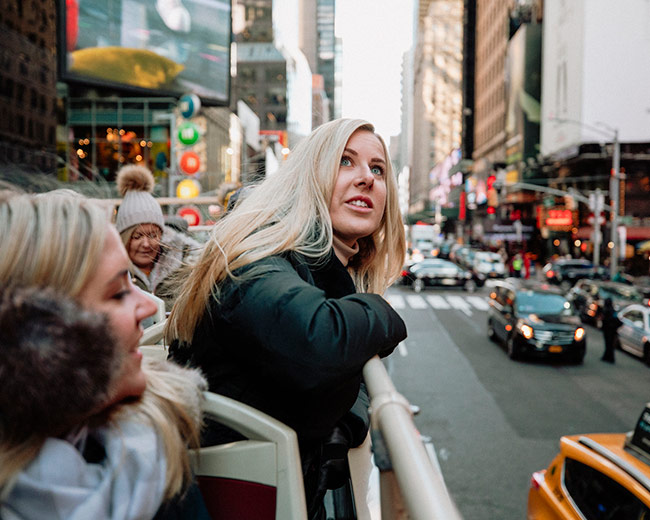 tourists in open roof bus in new york