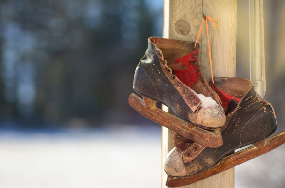 old, worn out ice skates hanging on wooden post