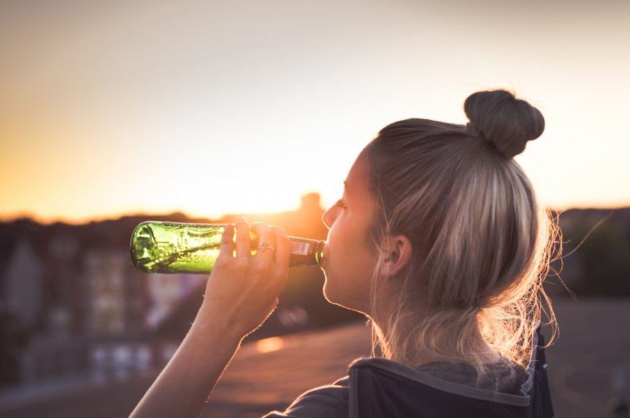 girl with her hair up drinking a beer with a sunset in the background