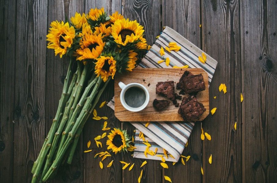 sunflowers next to a tray of brownies with coffee