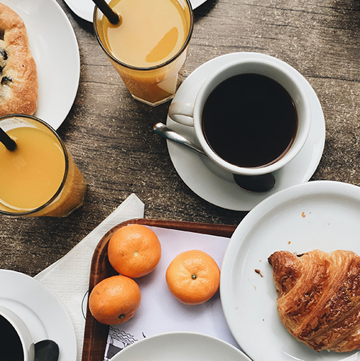 two glasses of orange juice, cup of coffee, and a tray with oranges and a croissant at a table