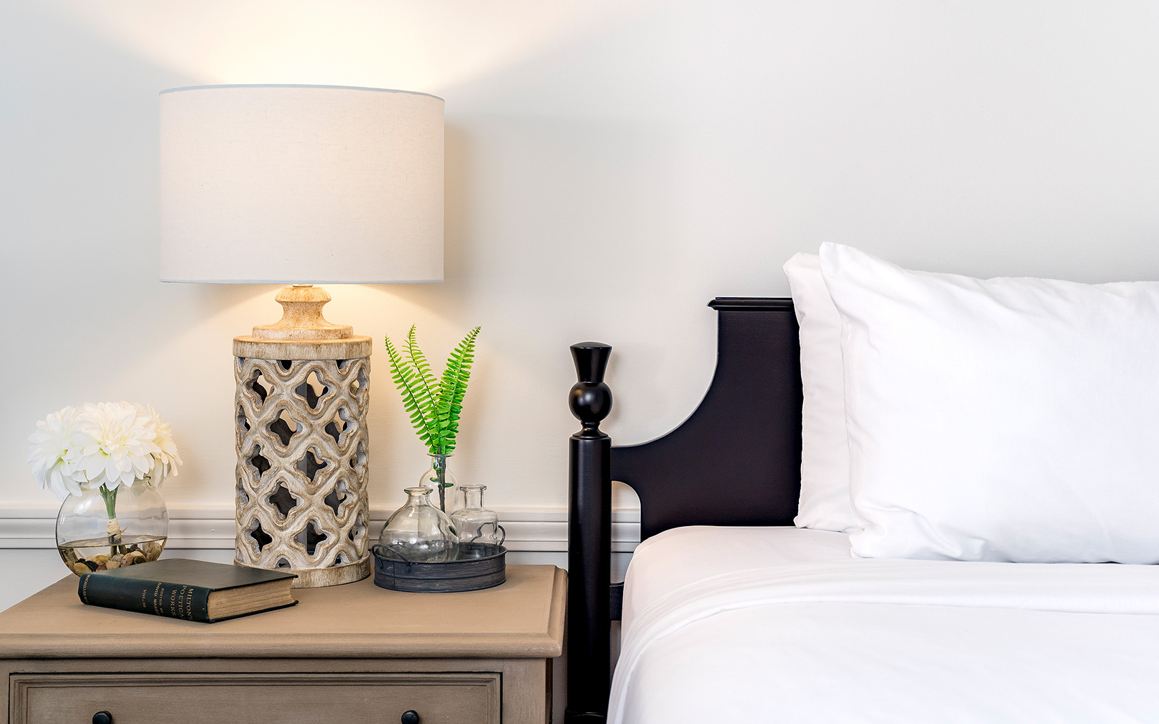 black headboard white sheets and tan lamp