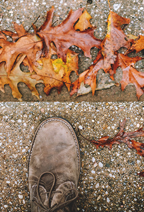 close up of a man's shoe standing on pavement near red fall leaves on the ground