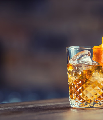 a bourbon drink with an orange twist garnish