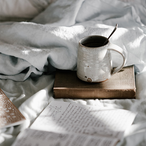 open journal on a messy bed next to cup of coffee sitting on a book