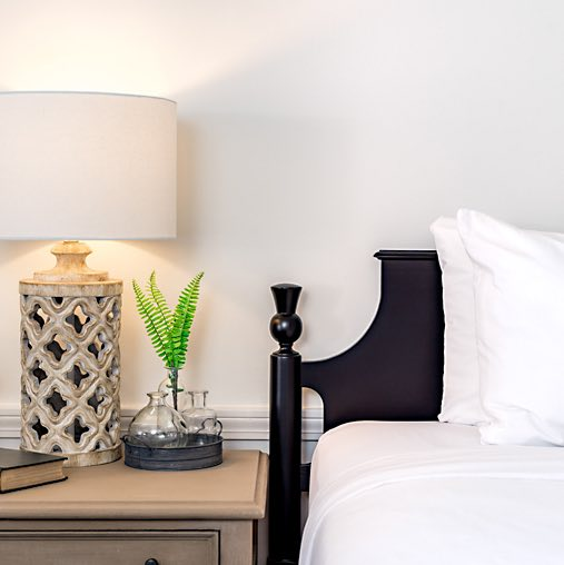 hotel bed with black headboard nightstand with lamp and plant