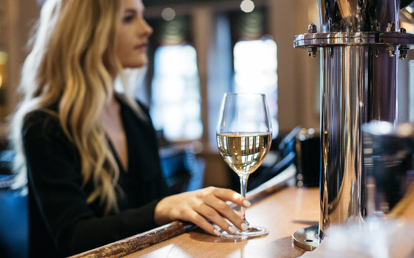 blonde woman at bar holding a white wine in glass