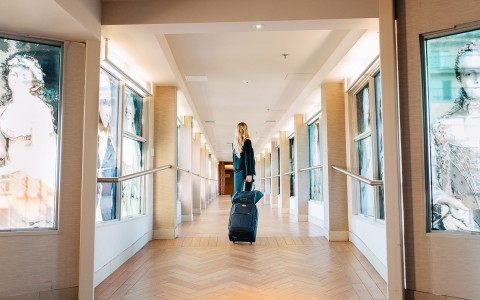 woman with luggage in hotel Hallway