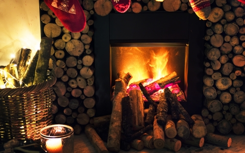 Blazing fireplace with logs stacked all around and Christmas stocking hung above