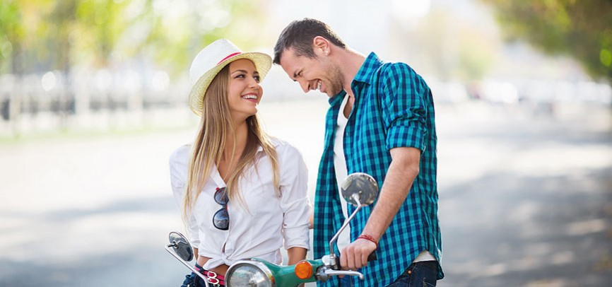 couple smiling by moped