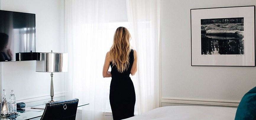 woman wearing black dress standing in hotel room