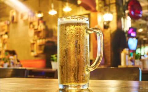 Tall glass of beer on bar in pub lit with bright golden light