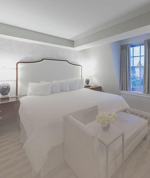 King bed with white sheets, lounger at foot of bed, two nightstands & window
