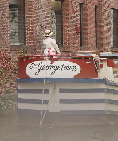 Woman wearing sun hat riding boat with The Georgetown written on it