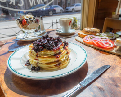 stack of blueberry pancakes on a white plate