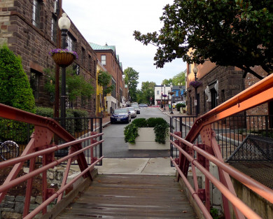 walkway bridge with red siding leading to downtown