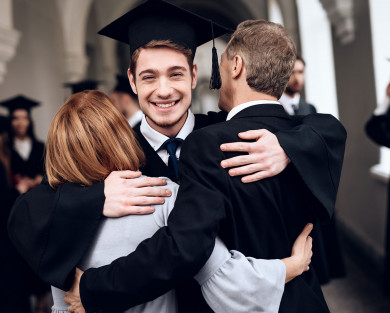 man hugging his parents on graduation day