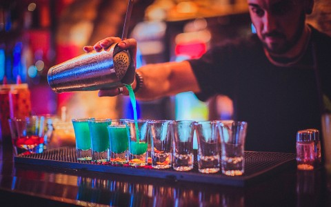 bar tender pouring bright green drink into several cups