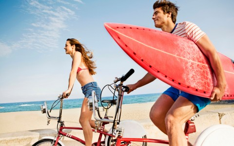 couple riding bikes while carrying a surf board