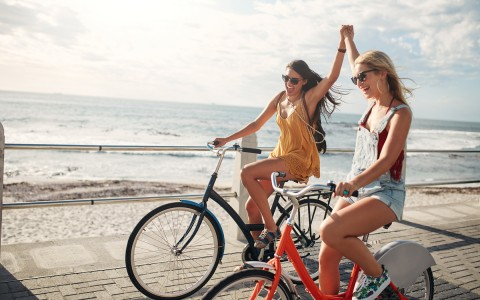 women riding bikes next the beach
