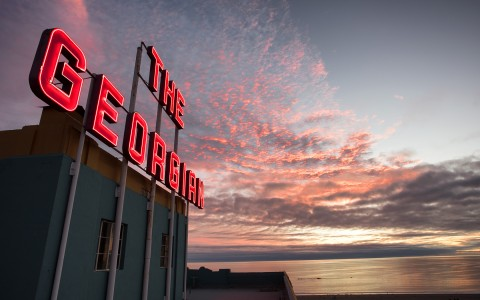 hotel sign in front of cotton candy pink skies