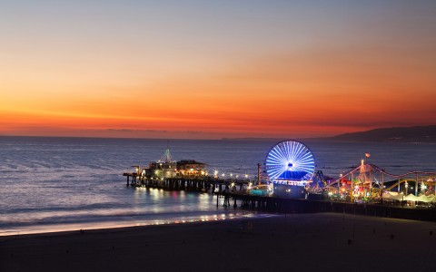 sunset by the malibu pier with colorful ferris wheel