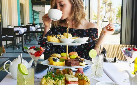 woman sipping on teacup in front of a table full of snacks