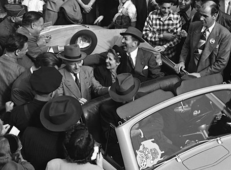 History image of people surrounding car
