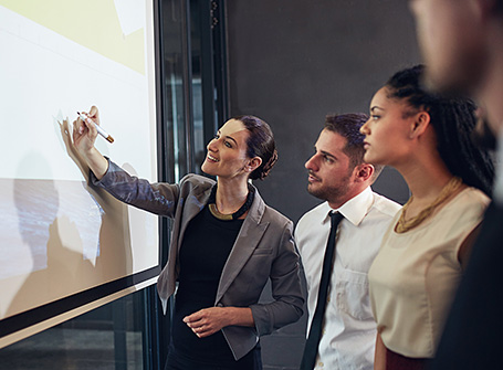 Business women and man reviewing a white board in a meeting