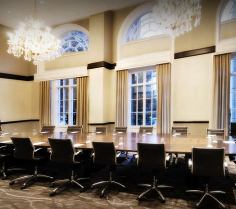 boardroom with floor to ceiling windows large chandeliers and a large table