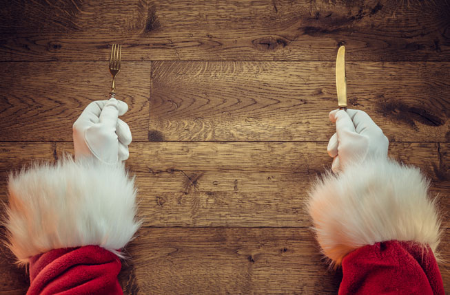 Santa Claus hands holding fork and knife