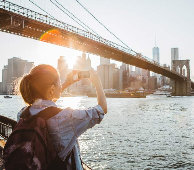 Girl taking a picture of the Brooklyn Bridge at sunset