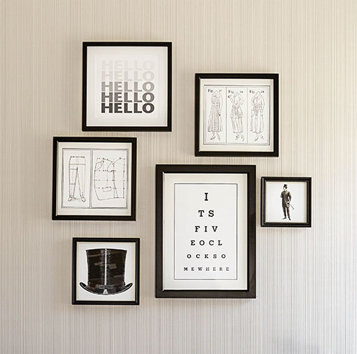 Different sized black frames with minimalistic art on wall