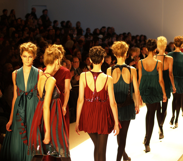 Women walking down catwalk during fashion show