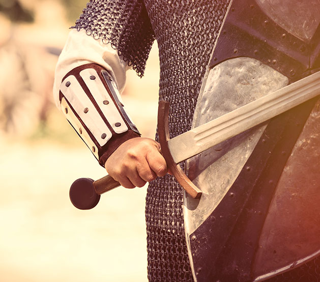 Close up of man wearing armor & carrying sword