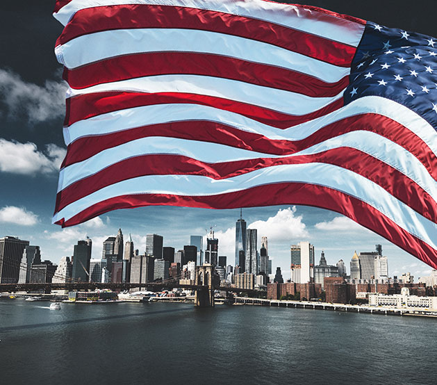 American flag waving in the wind with New York City in the back
