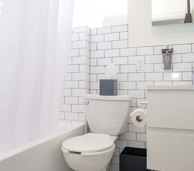 Full white bathroom with sink, toilet & shower with curtain