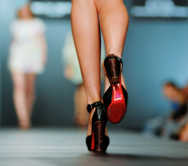 focus on womans shoes as she walks down the runway